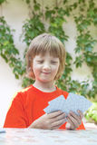 Boy with Blond Hair Playing Cards Stock Photo