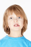 Boy with Blond Hair Showing his Missing Milk Teeth Royalty Free Stock Image