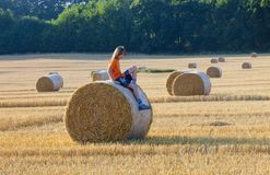 Boy Sitting on a Bale of Hay in Summer Royalty Free Stock Photos