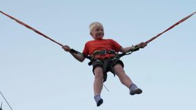 Boy blond jumps on trampoline.  stock video footage