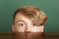 Boy with blond quiff looking over desk Royalty Free Stock Photography