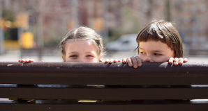Boy with blonde girl hiding on a street bench Royalty Free Stock Images