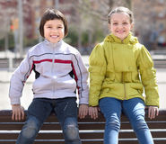 Boy with blonde girl sitting on bench outdoors Stock Photography