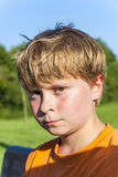 Boy with blonde hair looking serious Stock Photo