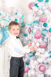 Boy blonde in white shirt and pants, standing near the Christmas tree. New Year. Christmas. Boy blonde in white shirt and pants, standing near the Christmas tree Royalty Free Stock Image