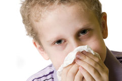 Boy blow nose open eyes. Frontal close-up of a seven-year Caucasian boy is cleaning with a tissue paper nose isolated on white Royalty Free Stock Photo