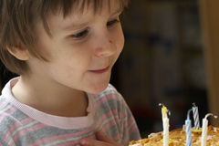 Boy blow out celebratory candles. The boy blow out celebratory candles on name day pie and thinks of desire Stock Photo