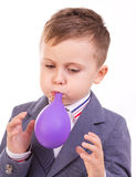 Boy blowing a balloon. Smiling little boy blowing a balloon isolated on white background royalty free stock photos