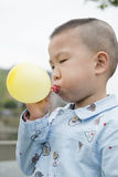 Boy blowing balloon Stock Images