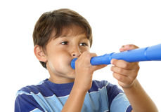 Boy blowing blue toy horn Royalty Free Stock Photos