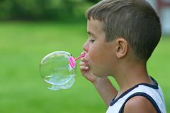 Boy Blowing Bubble. Boy blowing a bubble outdoors Stock Image