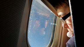 Boy blowing bubble while looking through aircraft window stock video footage