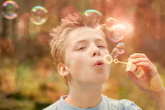 Boy blowing bubble outdoors Stock Photos