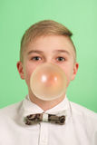 Boy blowing a bubblegum bubble. Boy blowing a bubblegum bubble isolated on green Royalty Free Stock Images