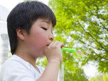 Boy blowing bubbles. Side view of Asian boy blowing bubbles Stock Image