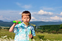 Boy blowing bubbles stock photo