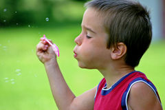 Boy Blowing Bubbles Stock Images