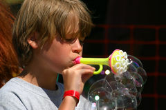 Boy blowing bubbles Stock Photos