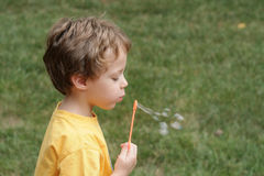 Boy blowing bubbles. Four year old child blowing bubbles Stock Image