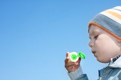 Boy blowing bubbles. Under sky Royalty Free Stock Photo
