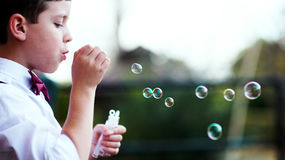 Boy blowing bubbles Stock Photography