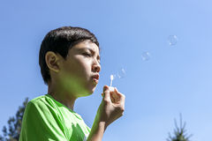 Boy blowing bubbles against blue skies. Young boy in green shirt blowing bubbles against blue skies on sunny day Stock Photos