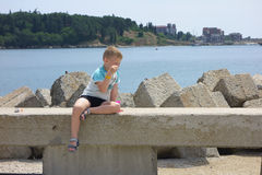 Boy blowing bubbles on the beach. Boy sitting by the sea on a concrete fence and blow bubbles Royalty Free Stock Photos