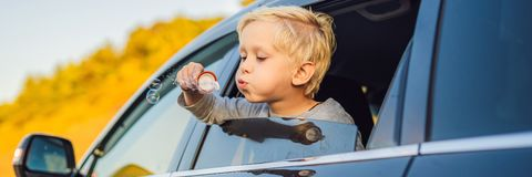 Boy blowing bubbles in the car window. Traveling by car with children BANNER, LONG FORMAT. Boy blowing bubbles in the car window. Traveling by car with children royalty free stock images