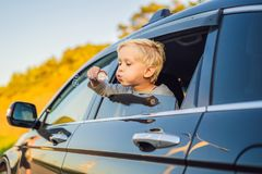 Boy blowing bubbles in the car window. Traveling by car with children.  stock image