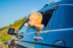 Boy blowing bubbles in the car window. Traveling by car with children.  stock photo