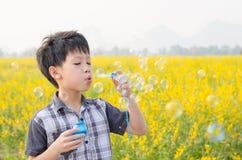 Boy blowing bubbles in flower field Stock Photo