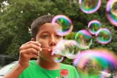 A boy blowing bubbles Stock Images
