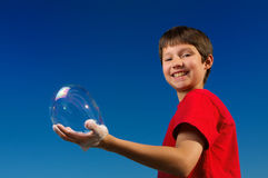 Boy blowing a bubbles and holding it in his hand !. Boy blowing a bubbles and holding it in his hand with a perfect blue sky Stock Photos