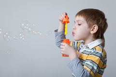 Boy blowing bubbles over grey Royalty Free Stock Photography