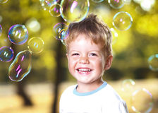 Boy blowing bubbles at the park Royalty Free Stock Photos