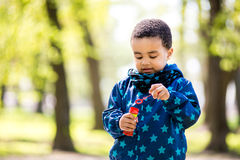 Boy blowing bubbles at the park stock photos