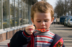 Boy blowing bubbles on the street Stock Photos