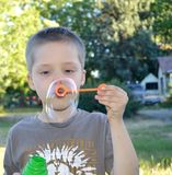 Boy blowing bubbles in the summer stock image