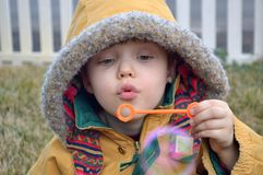 Boy blowing bubbles in the winter royalty free stock photos