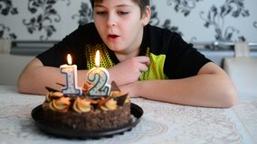 The boy blowing on  cake candles  with  number stock video