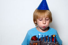 Boy blowing on the candles placed in the cake Royalty Free Stock Photo