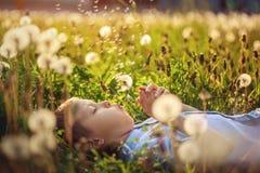 Cute boy blowing on dandelion lying on grass in sunny clear day. Boy blowing on dandelion lying on grass in sunny clear day stock photo