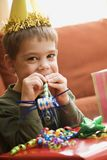 Boy blowing noisemaker. Caucasian boy at birthday party looking at viewer blowing noisemaker royalty free stock photography