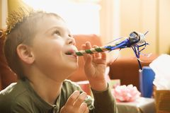 Boy blowing noisemaker. Royalty Free Stock Images