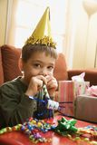 Boy blowing noisemaker. Caucasian boy at birthday party looking at viewer blowing noisemaker stock photo