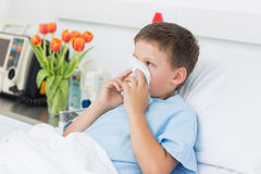 Boy blowing nose into tissue in hospital Royalty Free Stock Photos