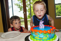 Boy blowing out birthday candle Royalty Free Stock Image