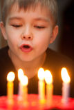 Boy blowing out candles on birthday cake Stock Images
