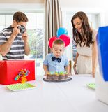 Boy Blowing Out Candles On Cake At Home Stock Image