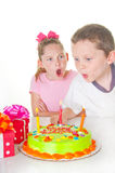 Boy blowing out girl's candles Royalty Free Stock Image